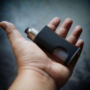 high end unregulated bottom feed squonk box mods with rebuildable dripping atomizer in hand on dark vignette fade to black texture background, vaping device