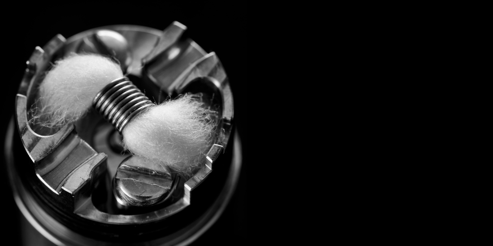 black and white, monochrome shot of single micro coil with japanese organic cotton wick in high end rebuildable dripping atomizer for flavour chaser, vaping device, vape gear, vaporizer equipment